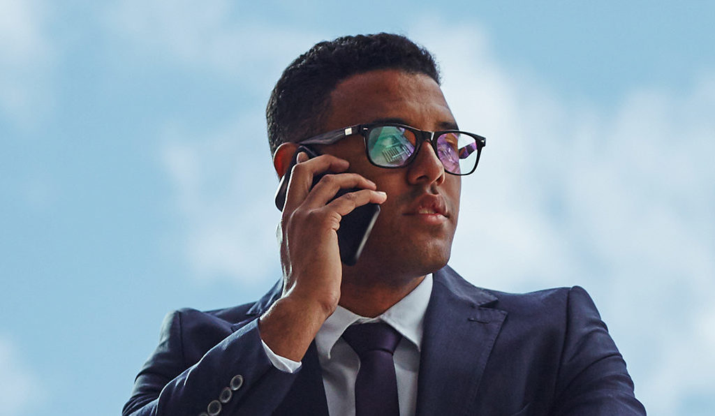 Young businessman speaking on mobile phone against cloudy sky